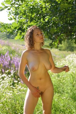 Curly nude girl in the garden