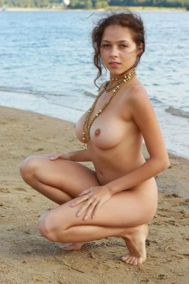 Sexy naked girl posing on the beach