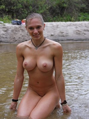 Busty nude girl swimming