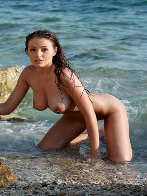 Naked busty woman swimming