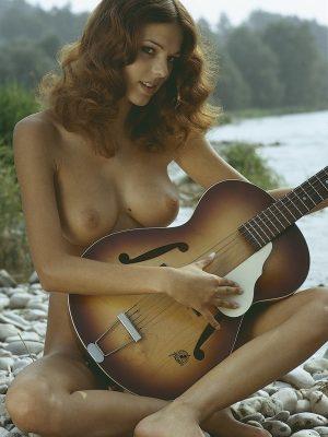 Nude girl playing guitar